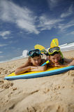 Brother and sister lying on the sand Stock Photography