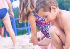 Group of litеle cute child makes sand castle at the beach. Brother and sister making sand castle at the beach royalty free stock photos