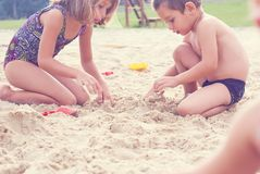 Group of litеle cute child makes sand castle at the beach. Brother and sister making sand castle at the beach stock image