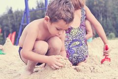Group of little cute child makes sand castle at the beach. Brother and sister making sand castle at the beach royalty free stock photos