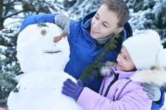 Brother and sister making a snowman. Outdoors in winter Stock Photos