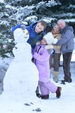 Brother and sister making a snowman. Grandparents on background Royalty Free Stock Photo