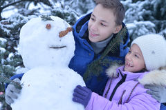 Brother and sister making a snowman. Outdoors in winter Royalty Free Stock Photo