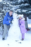 Brother and sister making a snowman. Outdoors in winter Royalty Free Stock Image