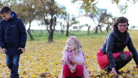 Brother, sister and mother are playing with yellow autumn maple leaves. stock video footage