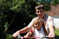 Brother and sister on a motorbike. Boy in the shirt sitting on the motorbike with a little girl royalty free stock image