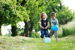 Brother and sister outdoor portrait with balloons. Portrait of cute brother and sister with blue balloons Royalty Free Stock Photo