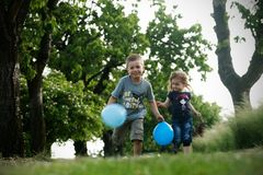Brother and sister outdoor portrait with balloons. Portrait of cute brother and sister with blue balloons Stock Photos