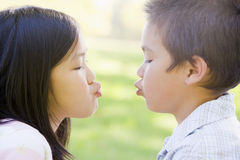 Brother and sister outdoors. With eyes closed puckering up Royalty Free Stock Images