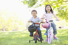 Brother and sister outdoors on bicycles smiling Stock Image