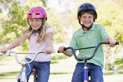 Brother and sister outdoors on bicycles smiling Stock Photo