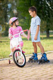 Brother and sister outdoors riding bikes and roller Royalty Free Stock Photography