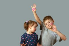 Brother and sister with painted hearts on the face and hands Stock Photos