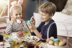 Brother and sister painting Easter eggs. Little kids during the painting eggs Stock Photos