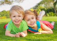 Brother and sister in the park. Picture of brother and sister having fun in the park, two cheerful child laying down on green grass, little girl and boy playing stock photo