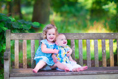 Brother and sister in a park. Adorable kids, little curly girl and a cute baby boy, brother and sister, sitting together on a wooden bench in a garden, hugging Stock Photography