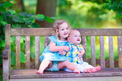 Brother and sister in a park. Adorable kids, little curly girl and a cute baby boy, brother and sister, sitting together on a wooden bench in a garden, hugging Royalty Free Stock Images