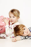 Brother and sister with piggy bank Stock Photos