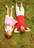 Brother and sister in pink dress lying on grass Royalty Free Stock Photography