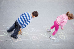 Brother and sister play hopscotch Stock Images