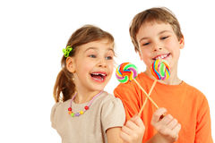 Brother and sister play with lollipops Stock Images