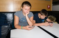 Brother and sister play with a smartphone waiting to have lunch Stock Images