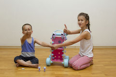 Brother and sister play with toys. Boy girl Royalty Free Stock Image