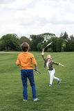 Brother and sister playing badminton on green grass. Cute brother and sister playing badminton on green grass stock images