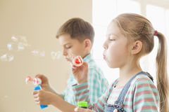 Brother and sister playing with bubble wands at home Royalty Free Stock Images
