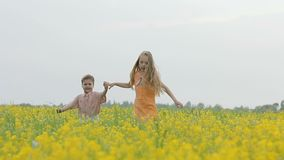Happy boy and girl having fun, running around the meadow with yellow flowers. Brother and sister playing in the canola field. Happy boy and girl having fun stock video