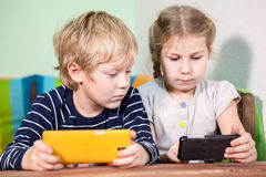Brother and sister playing with cellphones together Stock Images