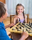 Brother and sister playing chess. Happy boy and little girl playing chess at home Stock Image