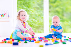 Brother and sister playing with colorful blocks Royalty Free Stock Photos