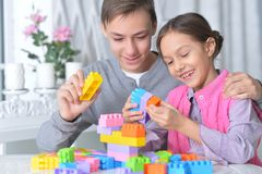 Brother and sister playing with colorful plastic blocks stock photo