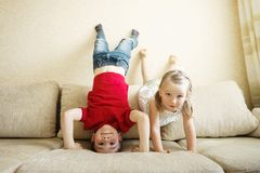 Brother and sister playing on the couch: the boy stands upside down. royalty free stock photos