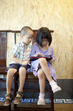 Brother and sister playing electric device. Young children sitting on chair at home, using laptop computer, looking at screen with serious expression Royalty Free Stock Images