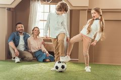 brother and sister playing football on yard of cardboard house while parents looking