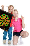 Brother and sister playing a game of darts. Isolated on white background Royalty Free Stock Photos