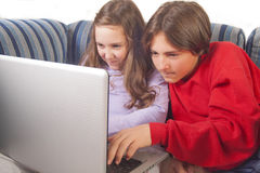 Brother and sister playing games on laptop Stock Photos