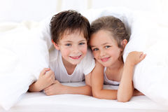 Brother and sister playing on parent's bed. Happy Brother and sister playing on parent's bed Stock Photos
