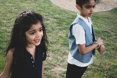 Brother and sister playing in a park outdoors. royalty free stock photo