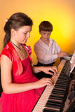 Brother And Sister Playing Piano. Piano player. Royalty Free Stock Image