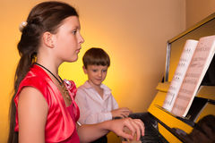 Brother And Sister Playing Piano. Piano player. Stock Photography