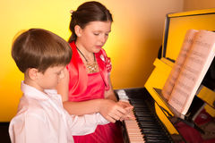 Brother And Sister Playing Piano. Piano player. Stock Photos