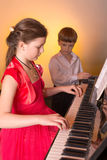 Brother And Sister Playing Piano. Piano player. Royalty Free Stock Photos