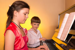 Brother And Sister Playing Piano. Piano player. Stock Images
