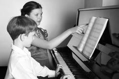Brother And Sister Playing Piano. Piano player. Stock Image