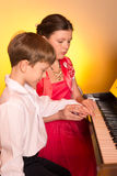 Brother And Sister Playing Piano. Piano player. Royalty Free Stock Images