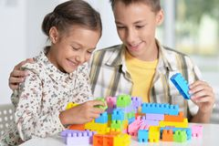 Brother and sister playing with plastic blocks. Brother and sister playing with colorful plastic blocks together Stock Image
