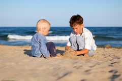 Brother and sister playing in sand at beach Stock Image